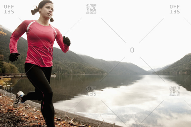 A female jogging along the Lake Crescent shore