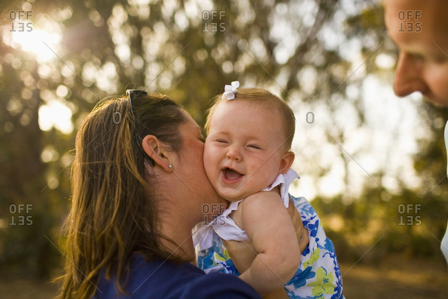 A baby girl smiles and squeals as her mother kisses her, while the sun flares through the trees in the background on a clear day in California