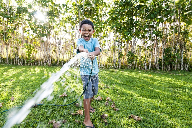 Boy spraying water from a hose, Cook Islands