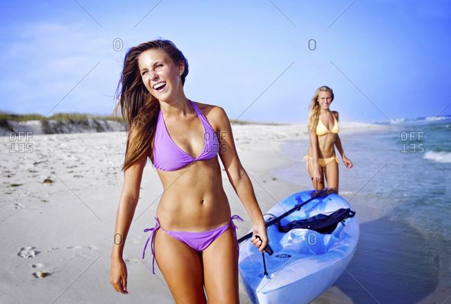 Two girls walk with a sea kayak along Pensacola Beach, Florida