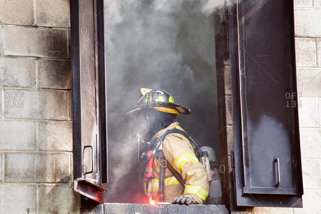 Fireman standing by the window of a burning building