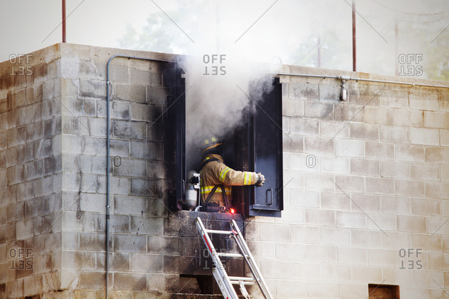 Fireman opening the window of a burning building