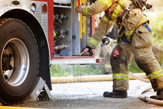 Fireman getting equipment from the fire truck