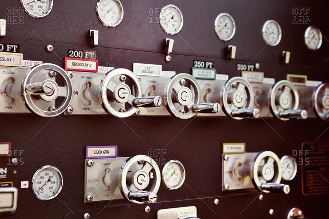 The control panel of a fire truck with numerous valves