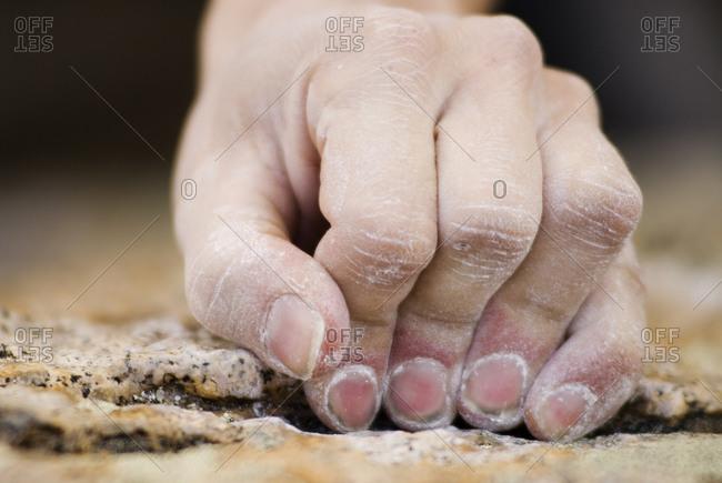 A rock climber's fingers grasp a small edge on a granite boulder near Bishop, California