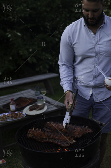 Man preparing barbecue ribs on garden party