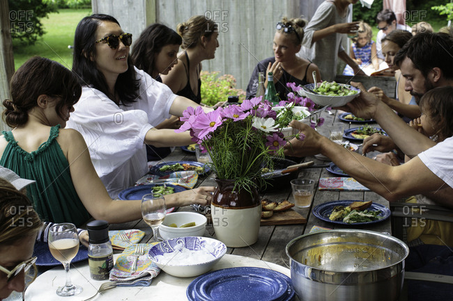 Young people eating and talking on garden party