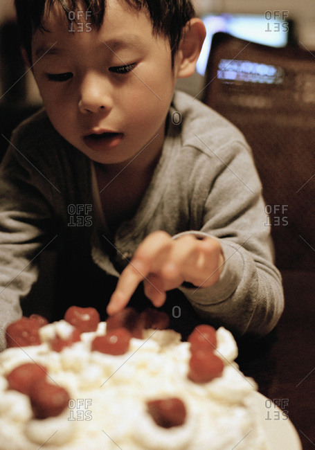 Child touching cherries on top of a cake