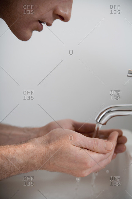 Man cupping hands under faucet