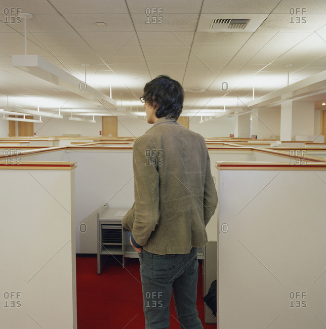 Young man looking over empty office cubicles