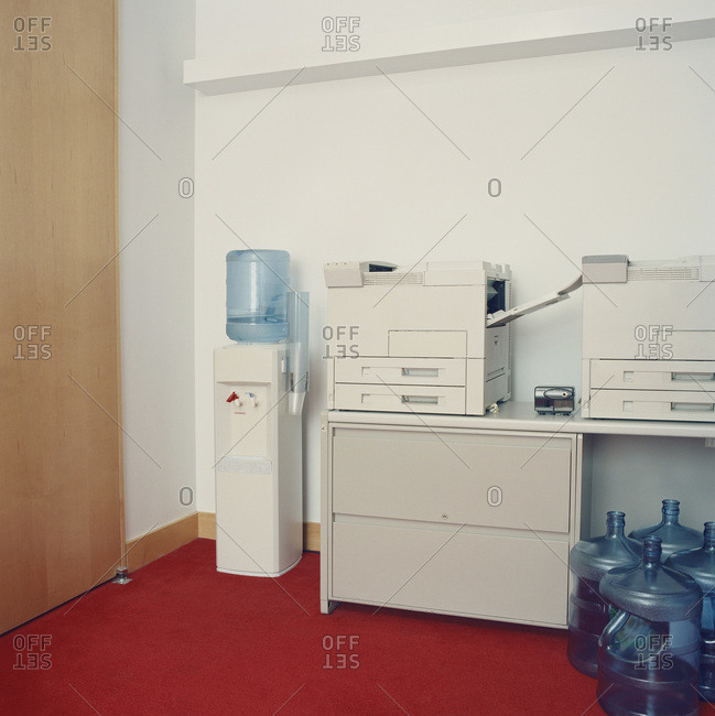 Photocopy machines next to water cooler in office