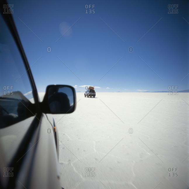 SUV's driving across salt flat, Salar de Uyuni, Bolivia