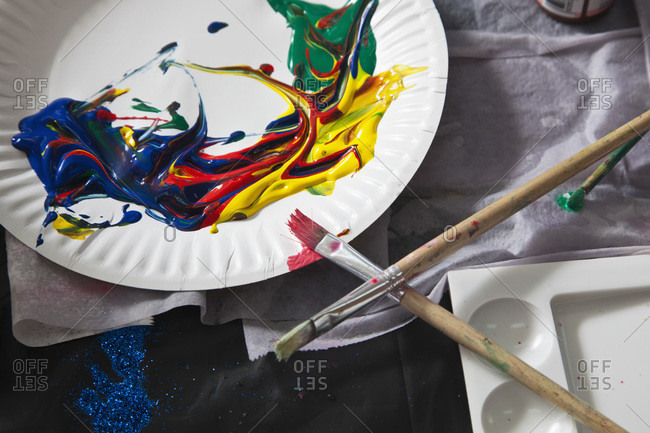 Heaps of acrylic paint on a paper plate and paintbrushes