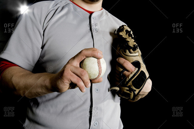 A baseball player holding a baseball, midsection view