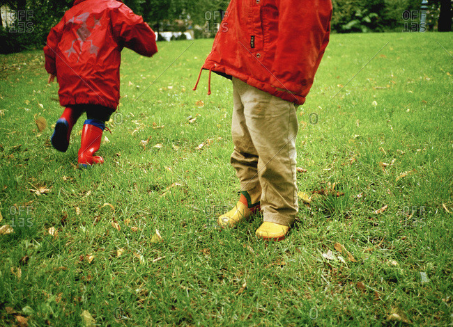 Children's rainboots on wet grass