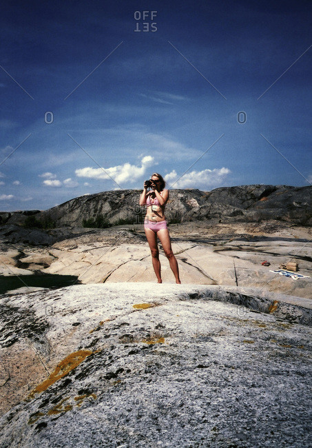 A woman standing on a large rock, taking a picture