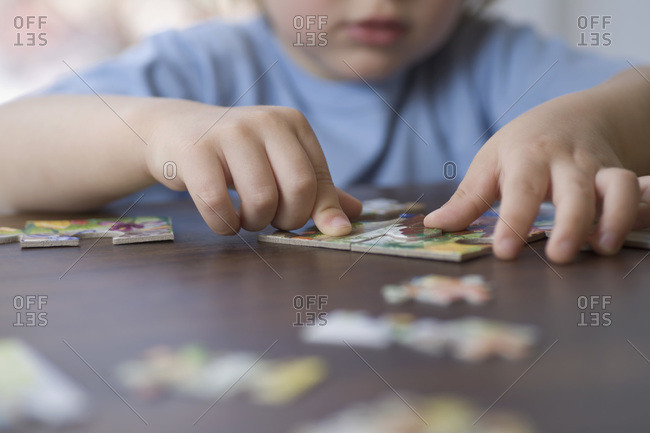 A young boy doing a jigsaw puzzle, focus on hands