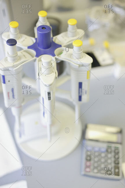 Rack of pipettes and calculator on bench in laboratory