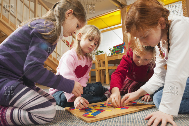 Children in nursery playing board game together in Germany