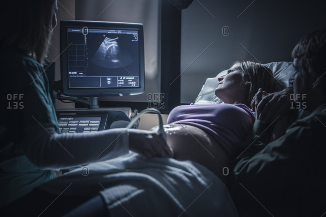 Pregnant couple having sonogram - Offset