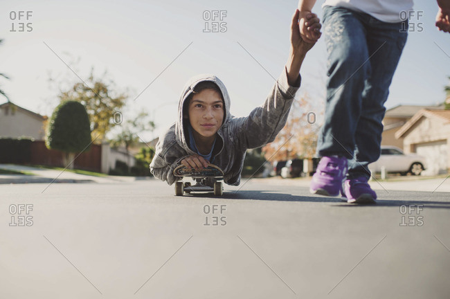 Little girl pulling boy on skateboard