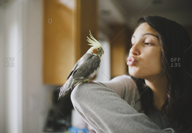 Young woman blowing kiss to parrot