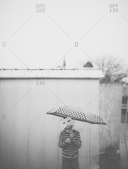 Little boy wearing mask and holding umbrella