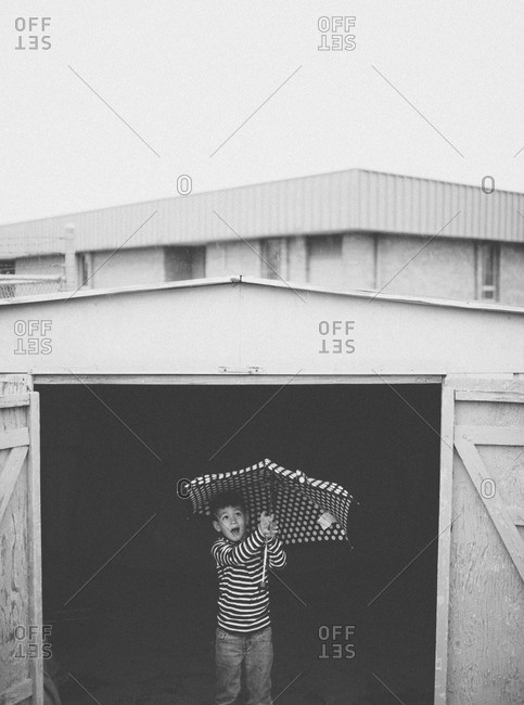 Little boy pointing and holding umbrella