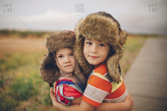 Little girl and boy wearing ear flap hat