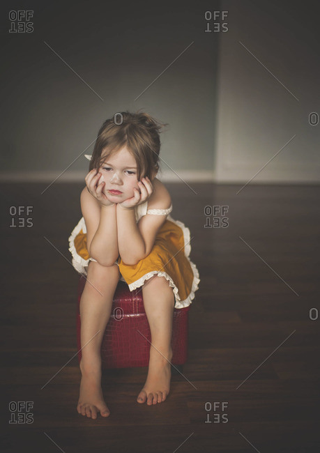 Young girl looking sad while sitting on stool