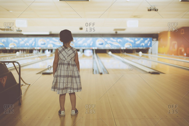 Young girl watching bowling lanes