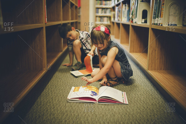 Young boy and girl playing in library