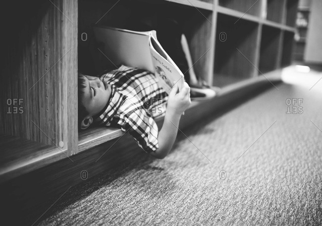 Young boy lying in bookcase reading