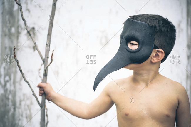 Boy wearing bird-like beak mask