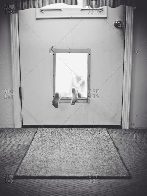 A baby escapes through the animal door flap