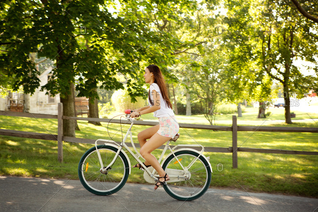 Side-view of brunette girl riding a bicycle in the park
