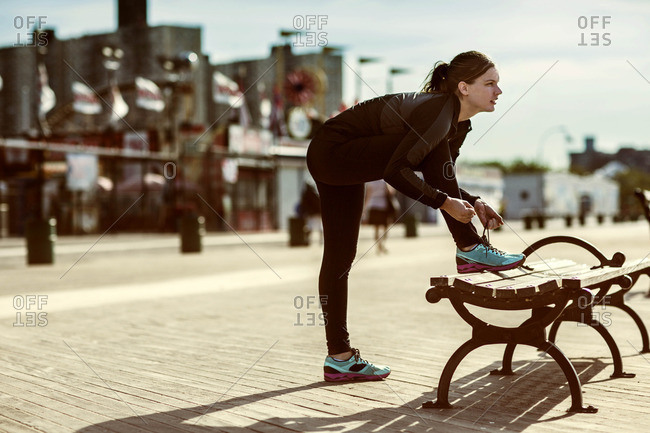 A runner ties her shoelaces