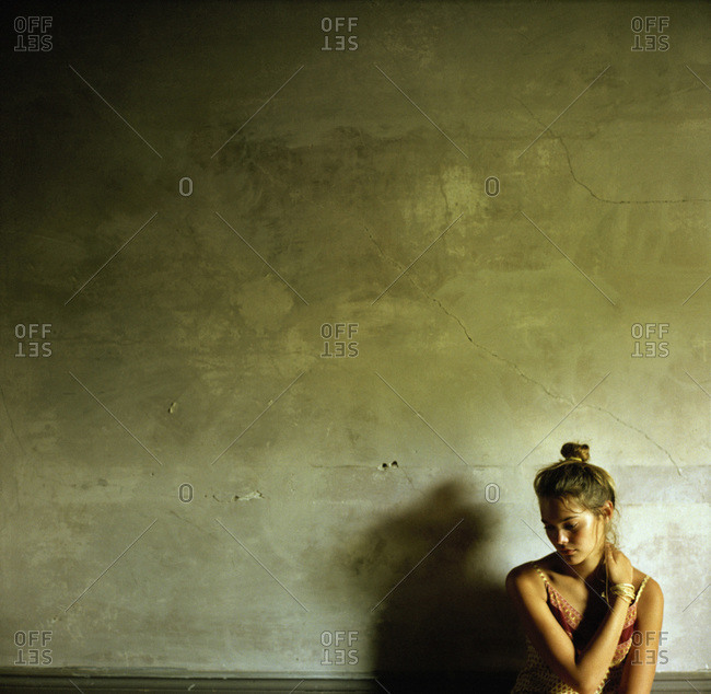 A young woman crosses her arms against a wall
