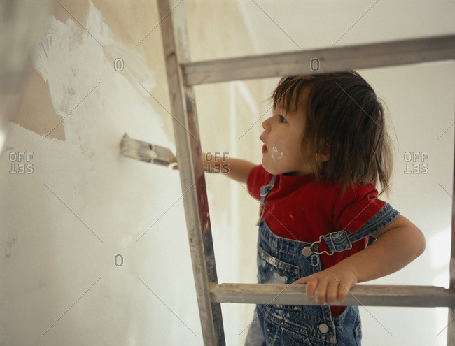 A young boy standing on a ladder and  painting a wall