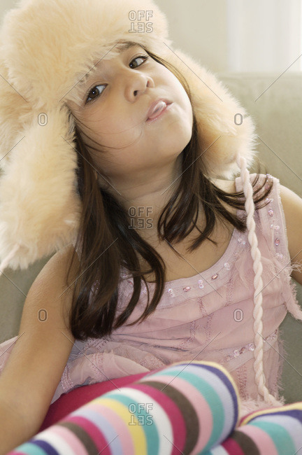 A young girl wearing a hunter's cap and blowing a bubble gum bubble