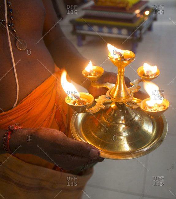 Burning coconut oil lamps in buddhist hand