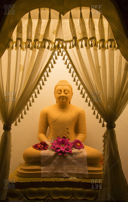 Ancient sitting Buddha statue with flowers