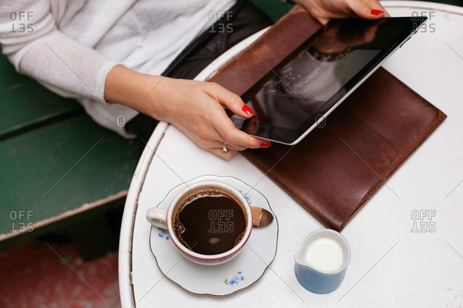 Hands of young woman holding a tablet in cafe