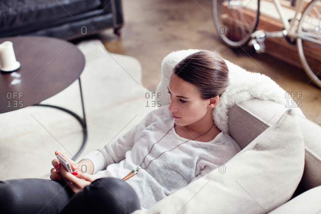 Young woman lying down on a sofa while texting
