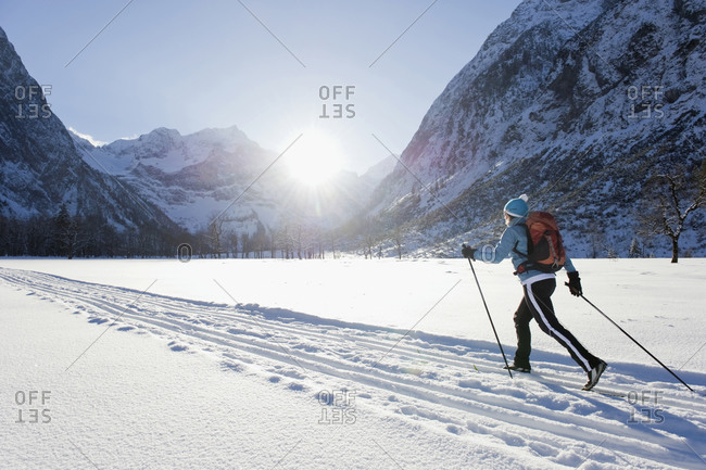 Senior woman doing cross-country skiing with karwendal mountains in background