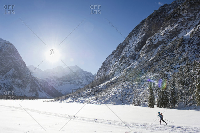 Senior woman doing cross-country skiing with karwendal mountains