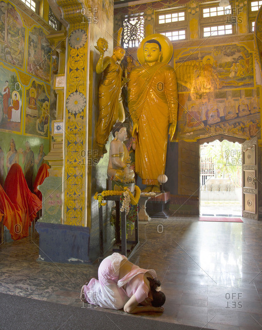 Temple interior with prayer woman in Colombo, Sri Lanka