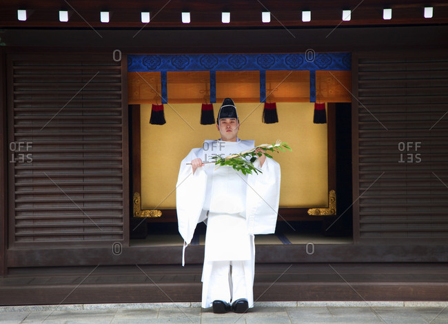Traditional dressed Shinto believer standing in front of shrine