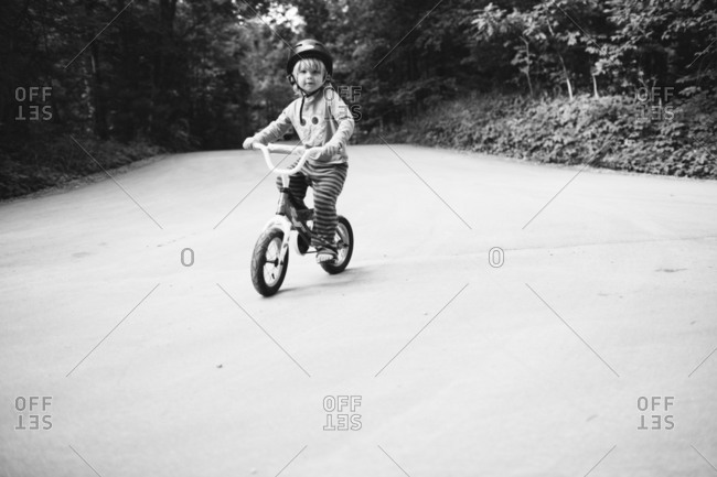 Little boy bicycling on the street and wearing helmet
