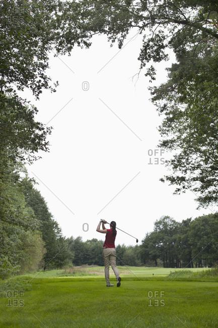A female golfer teeing off